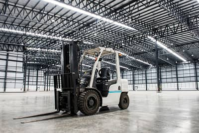 a forklift sitting in the middle of an empty hangar