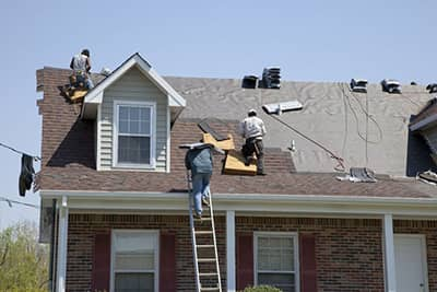 repair men replacing a roof on a home