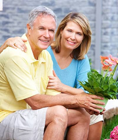 couple sitting on a bench smiling and holding a potted flower